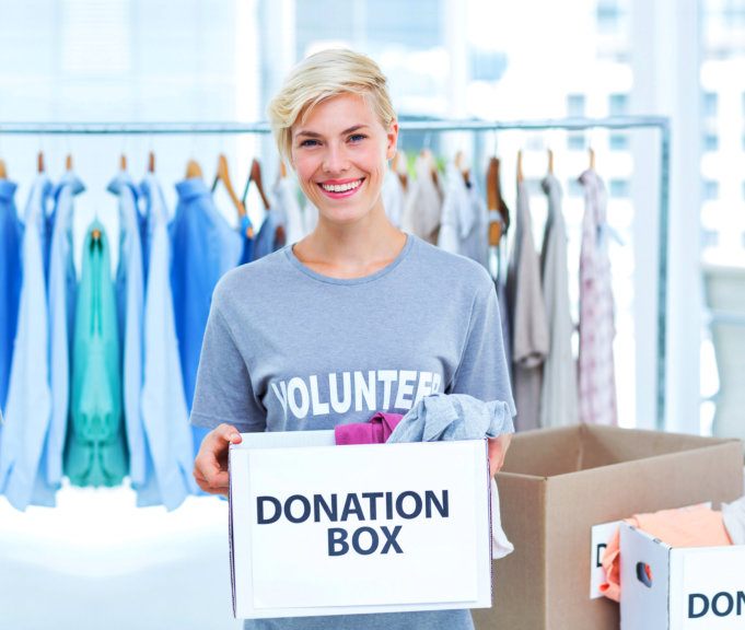 smiling woman while carrying a donation box